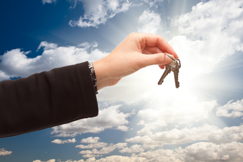 -female-holding-out-pair-of-keys-over-clouds-and-sky